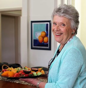 A picture of a woman with a plate of fruit