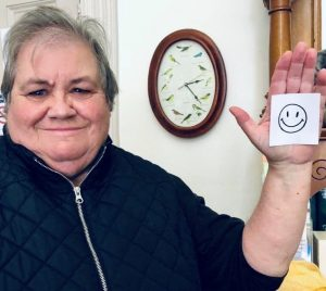 A volunteer with a smily face on a post it note stuck to their hand