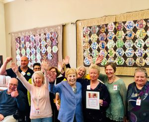 A group of people in front of patchwork displays on the wall