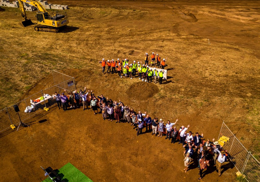 A bird's eye view of a groupd of people waving on a construction site